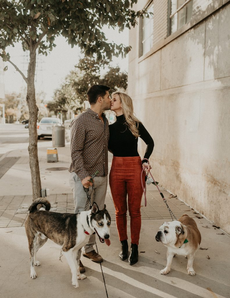 Engaged couple kiss as they walk during their engagement photos with dogs by Austin, Texas wedding photographer Nikk Nguyen.