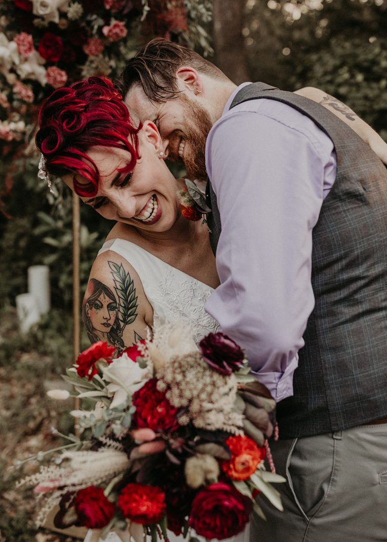 Bride and groom embrace while laughing during their intimate garden wedding in Austin, Texas. Image by Austin, TX wedding photographer Nikk Nguyen.