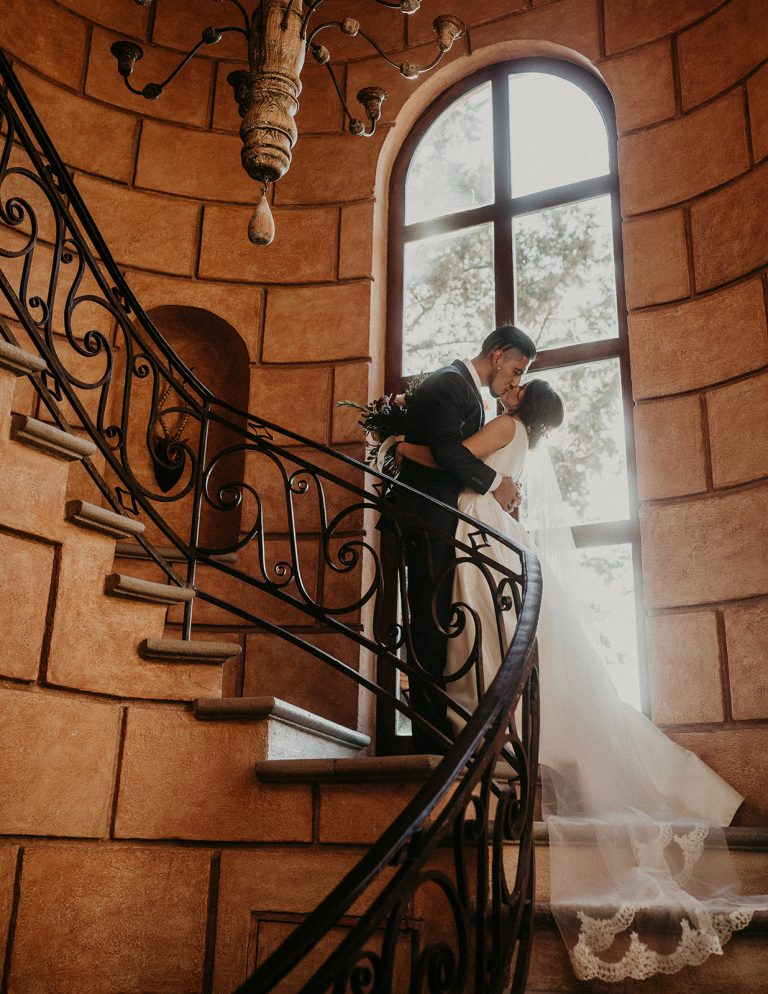Bride and groom embrace in a kiss on an elegant Spanish style staircase during their Casa Chorro Wedding in San Miguel de Allende, Mexico photographed by Austin, Texas wedding photographer Nikk Nguyen.