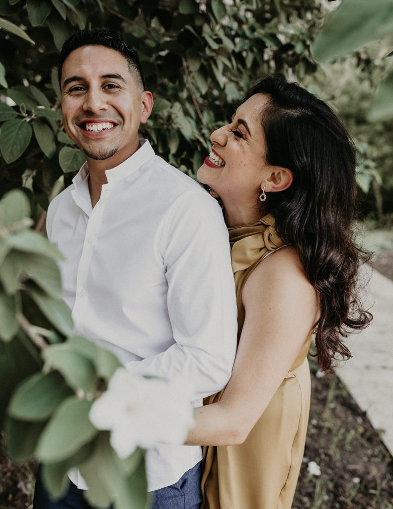 Bride to be embraces groom to be from behind as they smile during their Lost Pines Resort and Spa engagement shoot by Austin, Texas wedding photographer Nikk Nguyen.