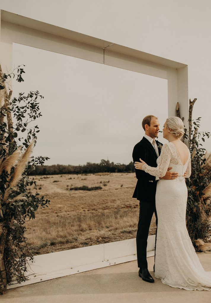 A bride and groom embrace at the altar during their wedding planned by Silver Thistle Weddings, one of the many Austin Texas wedding planners Image by Nikk Nguyen, an Austin, Texas wedding photographer.