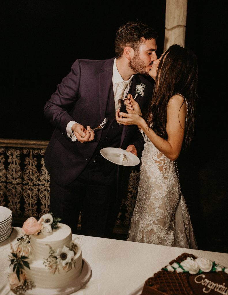 A bride and groom kiss after they've cut their cake together. Image by Austin, TX wedding photographer Nikk Nguyen.