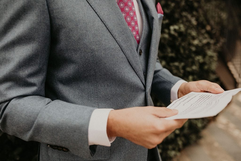 A close up of a groom reading a letter from his bride. Image by Austin, TX wedding photographer Nikk Nguyen.