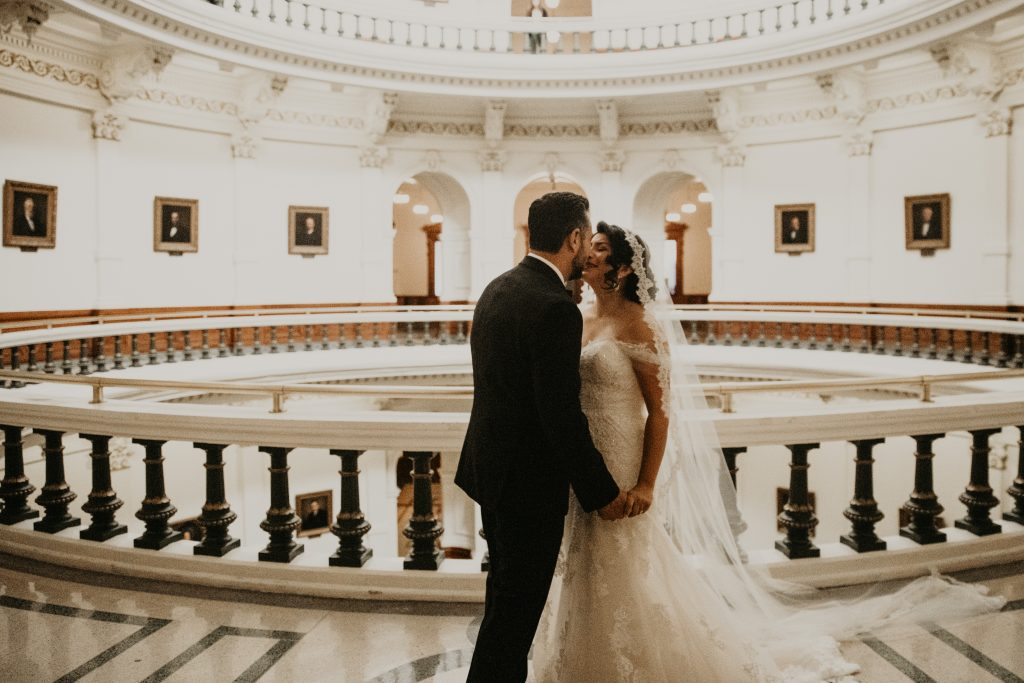 Bride and groom kiss in the elegant halls during their Texas State Capitol wedding in Austin, Texas. Photograph by Austin, TX wedding photographer Nikk Nguyen.