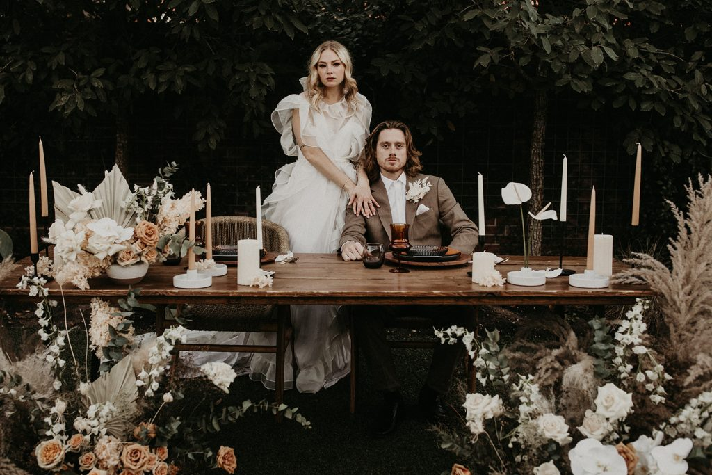 A bride and groom pose at a bohemian decorated table during their wedding inspiration shoot at The Union on Eighth photographed by Austin, Texas wedding photographer Nikk Nguyen during the Southern Love Workshop.