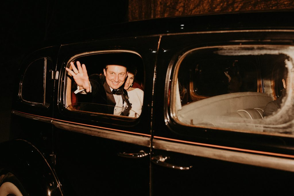 A groom waves goodbye from the exit car with his bride during their reception photographed by Austin, Texas wedding photographer Nikk Nguyen.