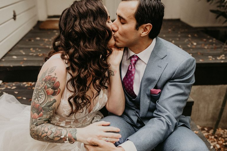 Bride and groom kiss while sitting on the steps of Hotel Saint Cecilia during their Vuka Bouldin Creek wedding in Austin, Texas. Photography by Austin, TX wedding photographer Nikk Nguyen.
