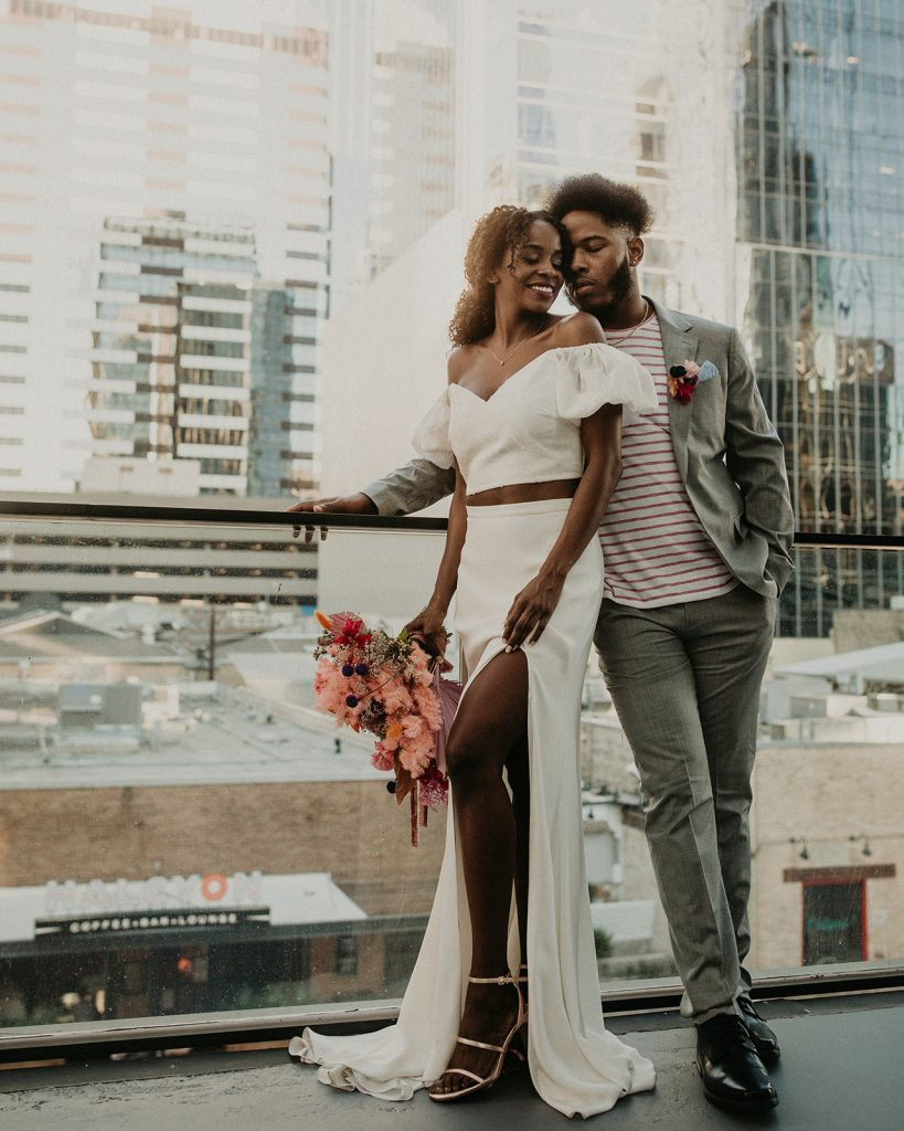 Bride and groom pose on the balcony during this '90s wedding inspiration shoot at the Riley Building in Austin, Texas photographed by Austin, TX wedding photographer Nikk Nguyen as part of the Southern Love Workshop.