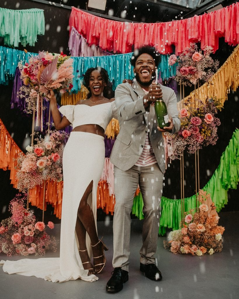 A newlywed couple celebrate their '90s wedding inspiration shoot by opening a bottle of champagne and smiling. Photograph by Austin, TX wedding photographer Nikk Nguyen.