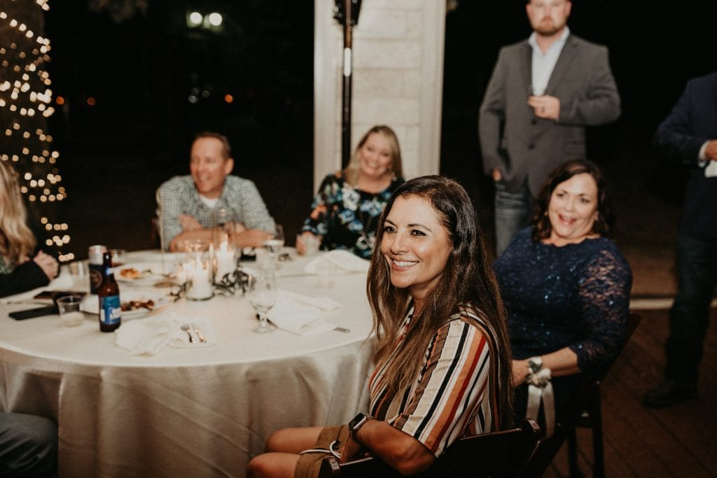 Wedding guests sit at their table during an unforgettable wedding speech after someone learned how to write a wedding speech. Image by Austin, Texas wedding photographer Nikk Nguyen.