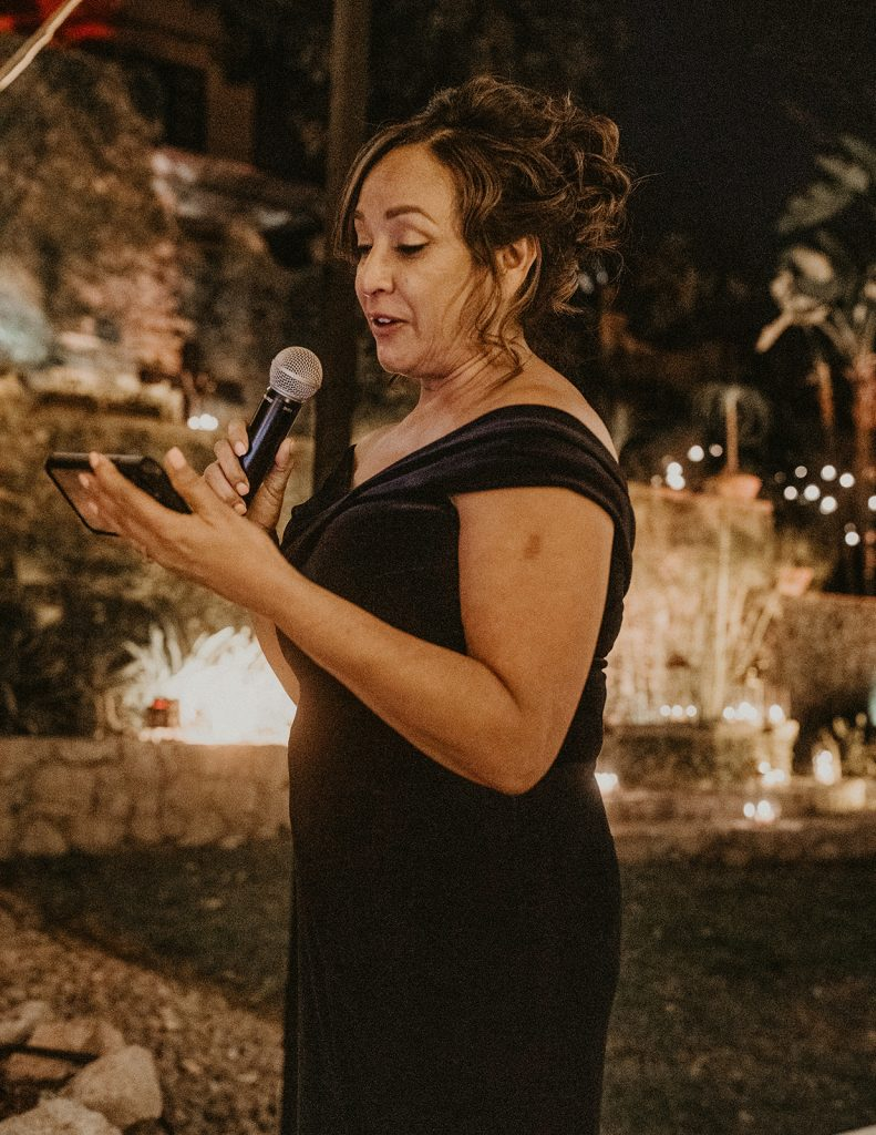 A loved one gives a wedding speech at an outdoor wedding in the evening. Image by Austin, Texas wedding photographer Nikk Nguyen.