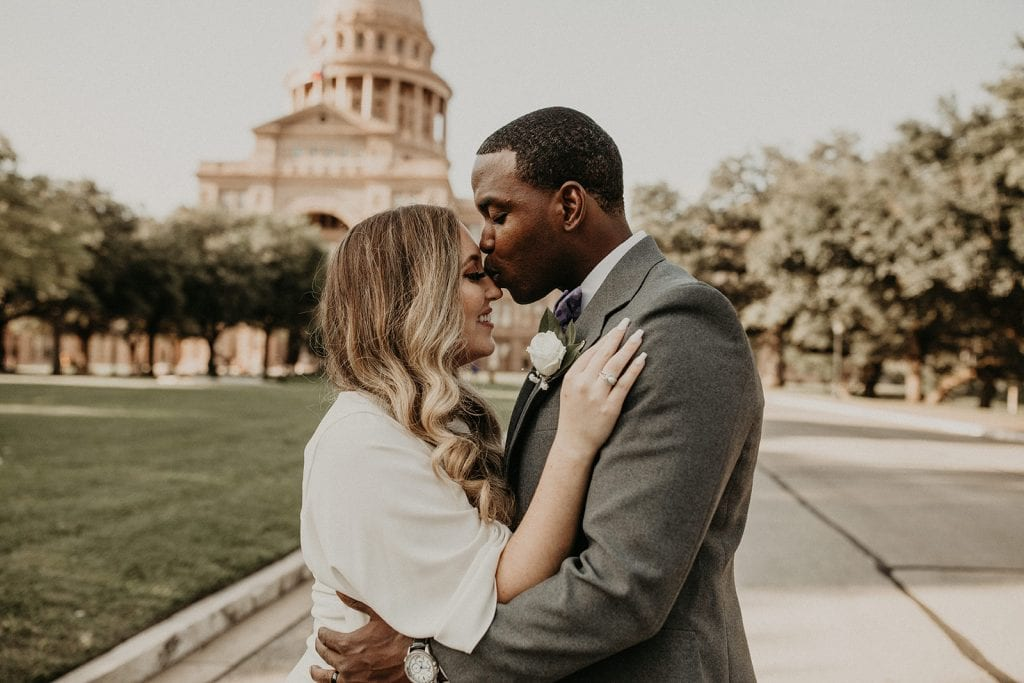 A newlywed couple embrace in front of the Capitol building during their Texas State Capitol Downtown Wedding photographed by Austin, TX wedding photographer Nikk Nguyen.