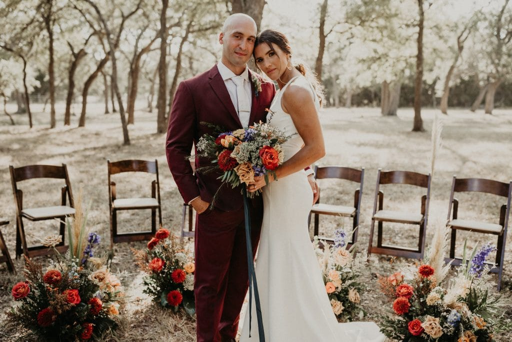 Bride and groom embrace while standing at the altar during their intimate whispering oaks estate wedding in Dripping Springs, Texas photographed by Austin, TX wedding photographer Nikk Nguyen.