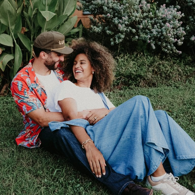 A couple cuddle each other and smile in a garden during their Urban Lifestyle Couples Shoot photographed by Austin, Texas wedding photographer Nikk Nguyen.