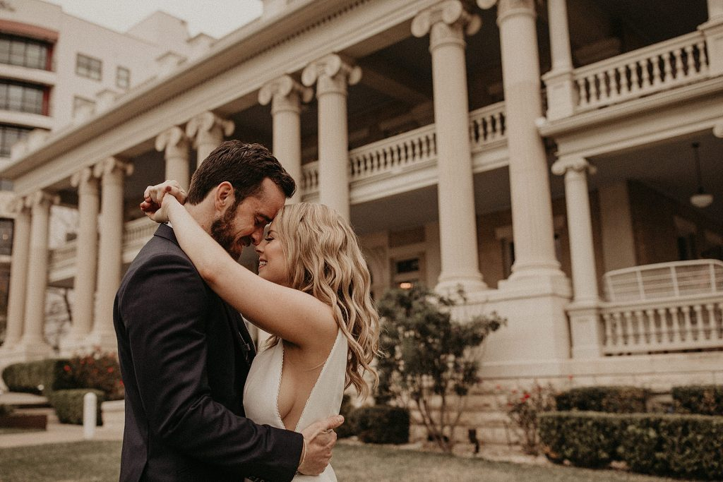 Bride and groom embrace in front of the stylish historic mansion during their wedding at Hotel Ella in Austin, Texas. Photograph by Austin, TX wedding photographer Nikk Nguyen.