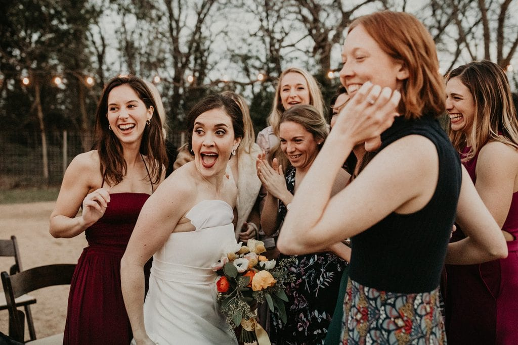 Bride smiles with her bridal party about the bouquet toss. Image by Austin, TX wedding photographer Nikk Nguyen.