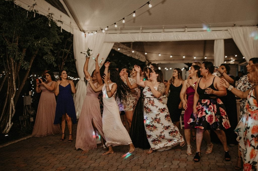 Bridal party and wedding guests reach to catch the bouquet thrown by the bride. Image by Austin, Texas wedding photographer Nikk Nguyen.