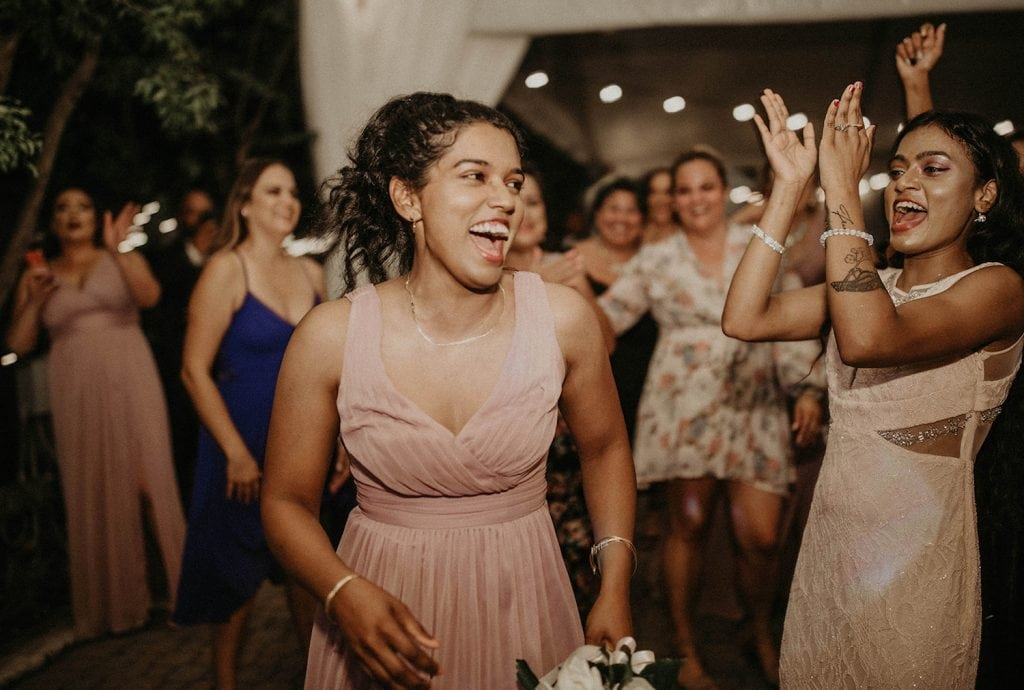 Bridesmaid smiles after catching the bouquet during the bouquet toss.