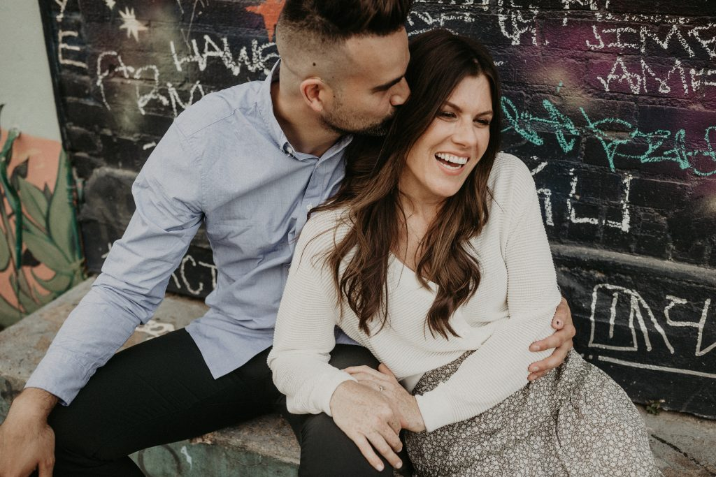 A man kisses his girlfriend on the head while they're sitting in front of a graffiti wall together and she's smiling during their Montopolis bridge Engagement Shoot photographed by Austin, Texas wedding photographer Nikk Nguyen