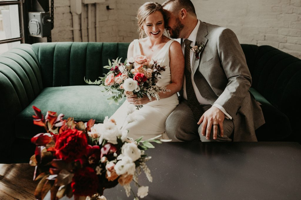 Bride and groom sit cuddled together on a couch during their One Eleven East wedding photographed by Austin, TX wedding photographer Nikk Nguyen.
