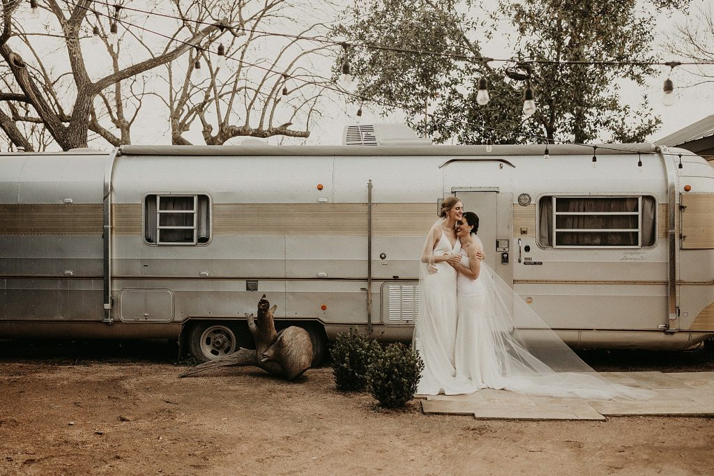 Brides embrace while smiling in front of a trailer during their Springdale Station Wedding in Austin, Texas. Photograph by Austin, TX wedding photographer Nikk Nguyen.