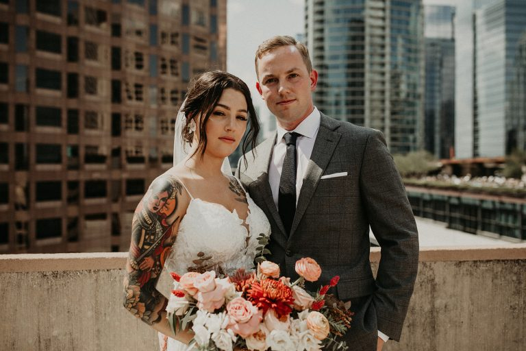 Bride and groom pose on top of a building in East Austin before their micro wedding photographed by Austin, TX wedding photographer Nikk Nguyen