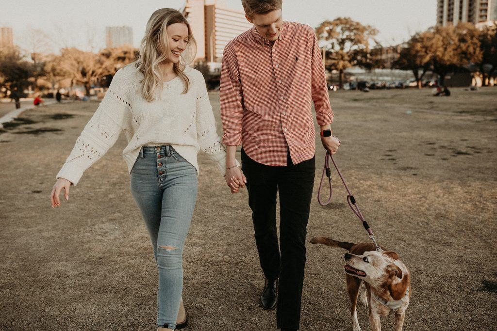 A couple hold hands while walking their dog during their engagement shoot by Nikk Nguyen Photo