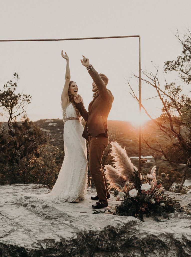 A bride and groom celebrate at the altar during golden hour of their elopement by Nikk Nguyen Photo