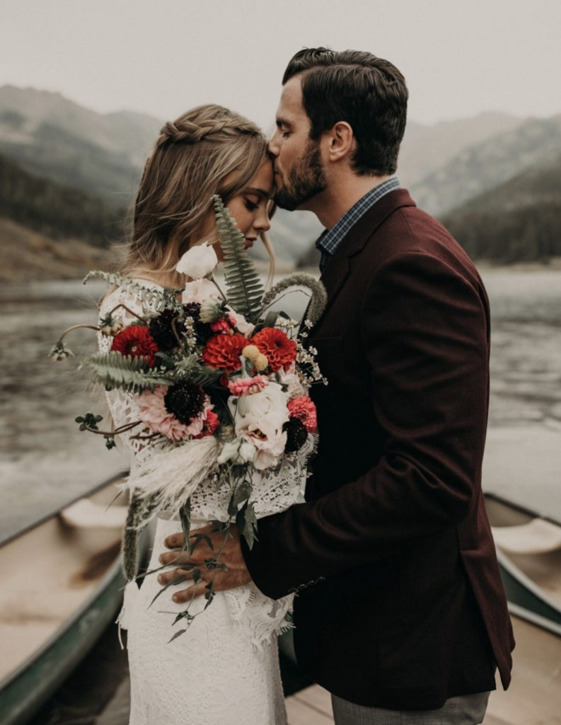 A groom kisses a bride on her forehead during their elopement in the Colorado Rockies