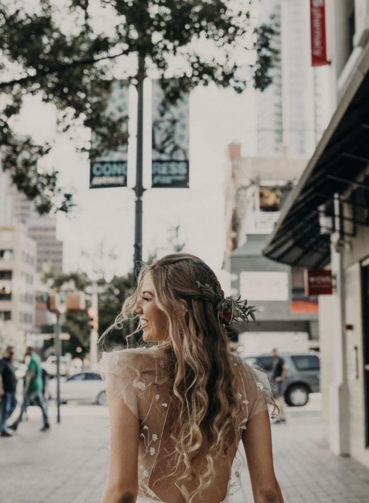 A bride smiles over her shoulder as she walks through Austin, Texas during her elopement