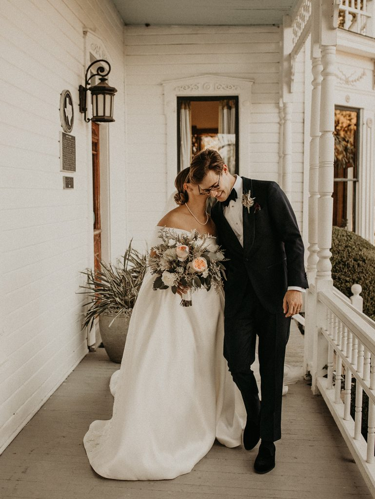 A bride whispers to her groom as they walk on the porch of their wedding venue during their elopement