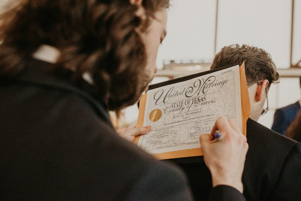 A bride signs her marriage certificate after her elopement in Austin, TX