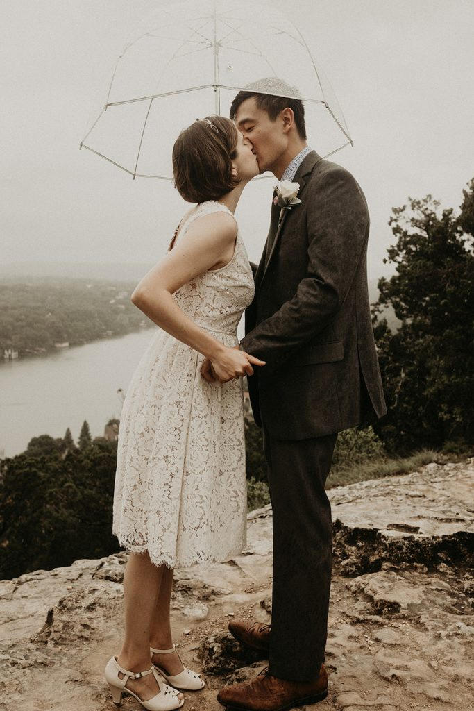 A newlywed couple kiss on top of Mt Bonnell during their elopement in Austin, TX
