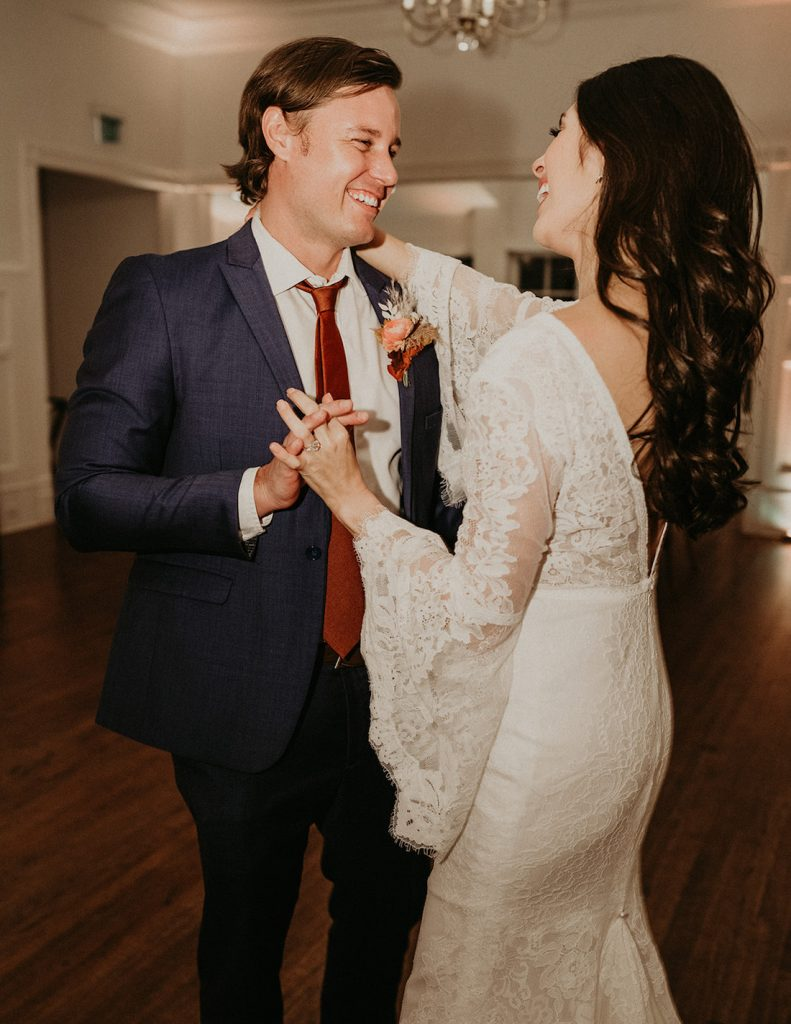 Bride and groom smile playfully at each other as they dance on their wedding night, captured by Austin, Texas photographer Nikk Nguyen
