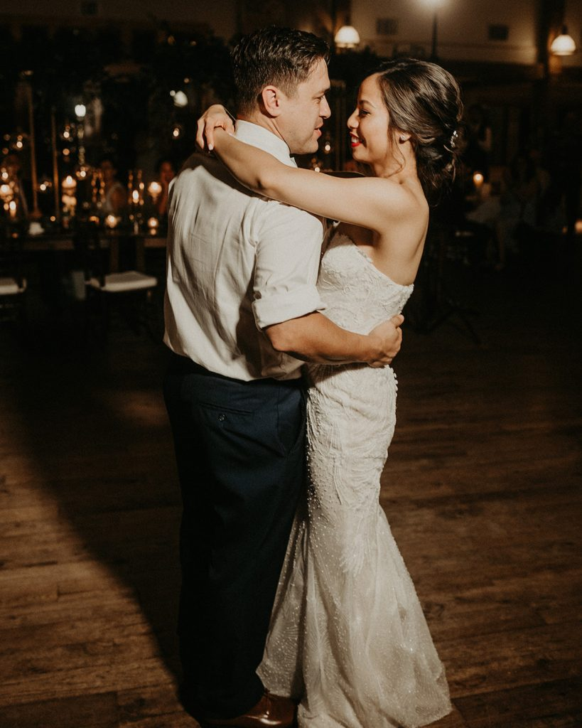 Bride puts her arms around groom's neck as he holds her waist during their first wedding dance, shot by wedding photographer Nikk Nguyen