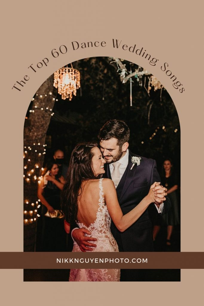Bride and groom smiling during their first dance at their wedding night; image overlaid with text that reads The Top 60 Dance Wedding Songs