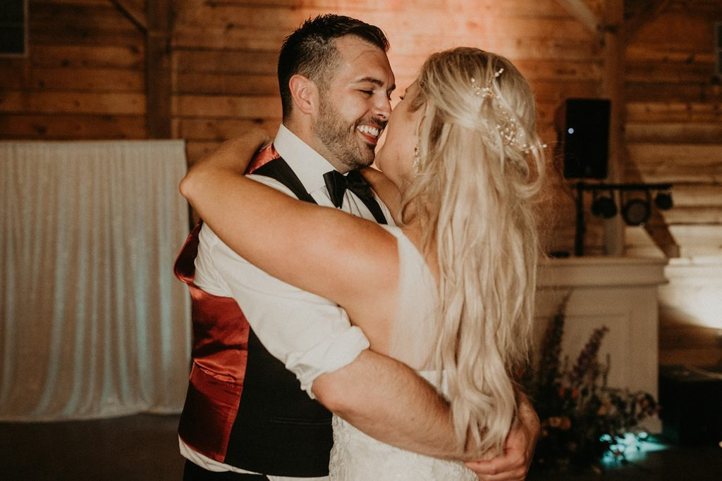 Couple smile and share an embrace as they dance to their first wedding dance, taken by Austin, Texas wedding photographer Nikk Nguyen