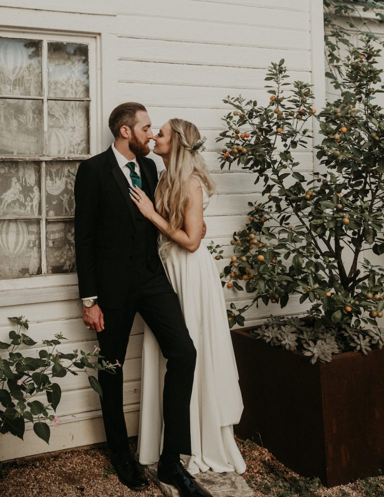 Bride and groom leaning up against a white wall with a window during their elegant wedding in Austin, TX taken by Nikk Nguyen