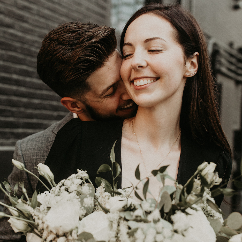 Groom kisses bride from behind as she smiles while holding her floral bouquet during their elopement in Austin, TX