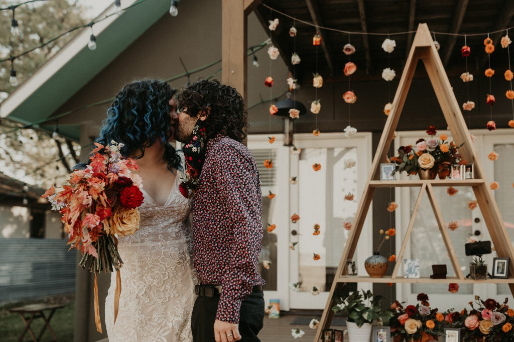 Bride and groom share a kiss in front of their makeshift wedding backdrop during their intimate backyard wedding in Austin, Texas captured by Nikk Nguyen Photography