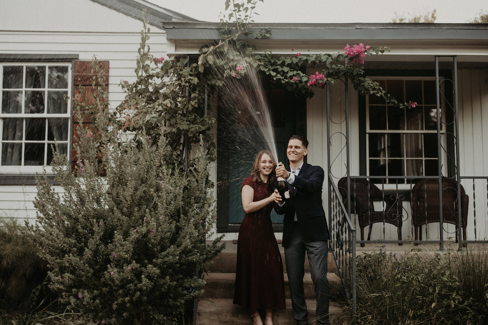 Couple pop a bottle of champagne in front of a house in East Austin during their engagement shoot, shot by Nikk Nguyen Photography