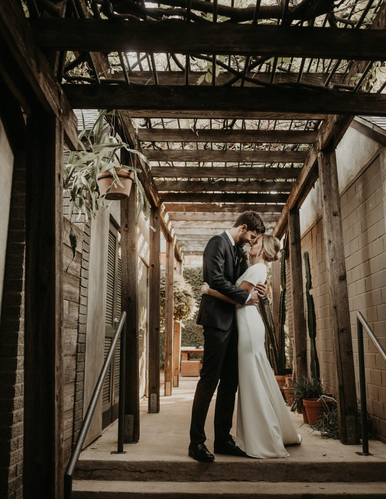 Bride and groom embrace and lean their heads together while standing in a corridor during their Hotel San Jose Austin wedding by Nikk Nguyen Photo