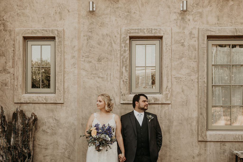 Bride and groom looking in opposite directions as they pose hand in hand in front of a plain cement wall with windows