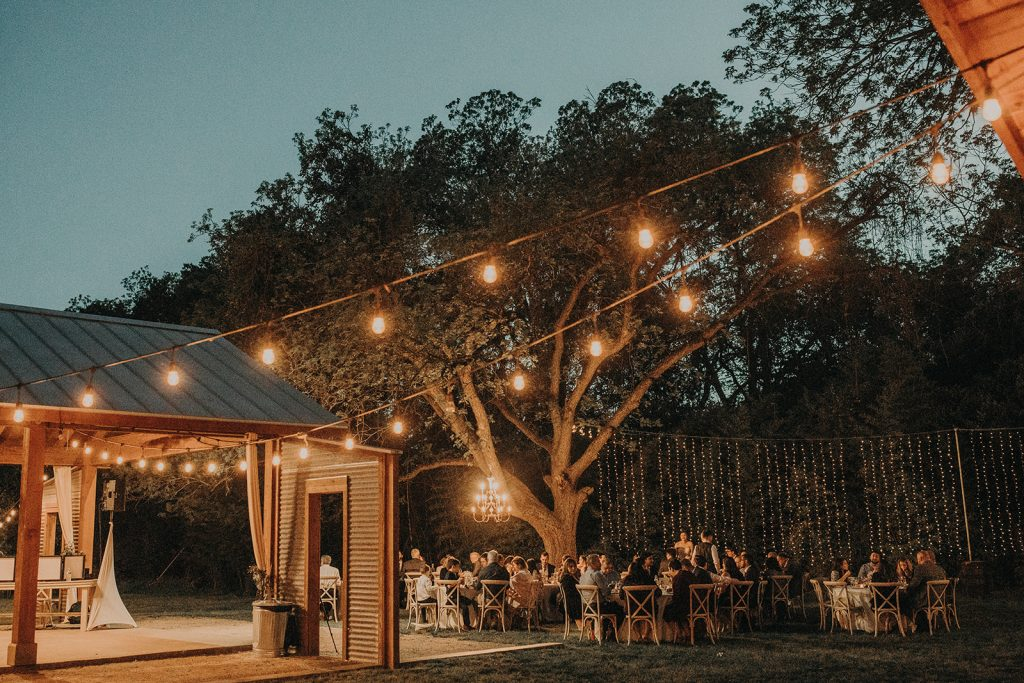 View of the outside terrace of Lake Travis Waterfront Retreat, Austin with lights and people gathered during a wedding reception