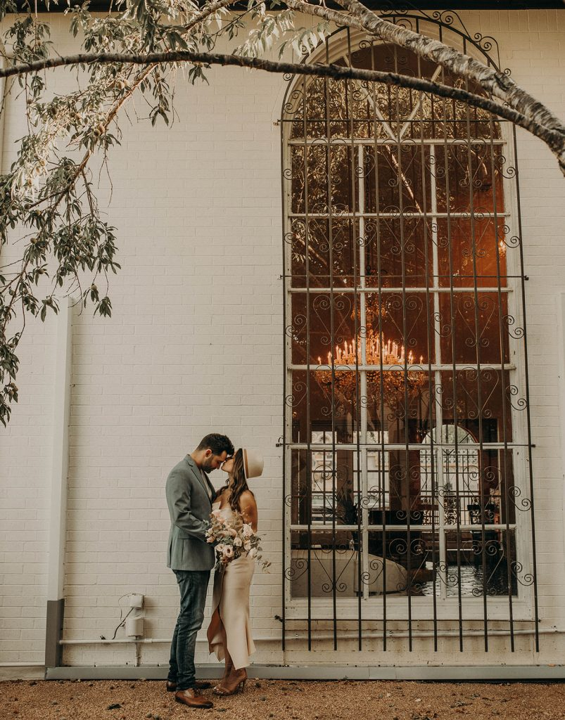 Bride and groom posing and sharing a hug outside the Historic Manor House, Austin