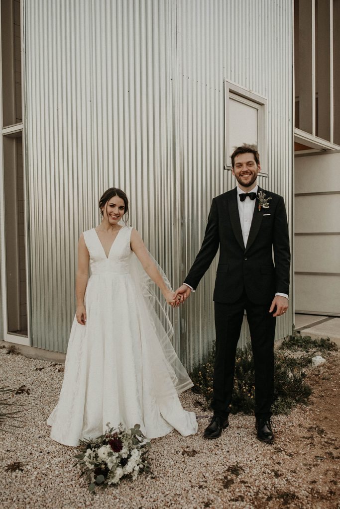 Bride and groom posing in front of the D6 Retreat, Dripping Springs